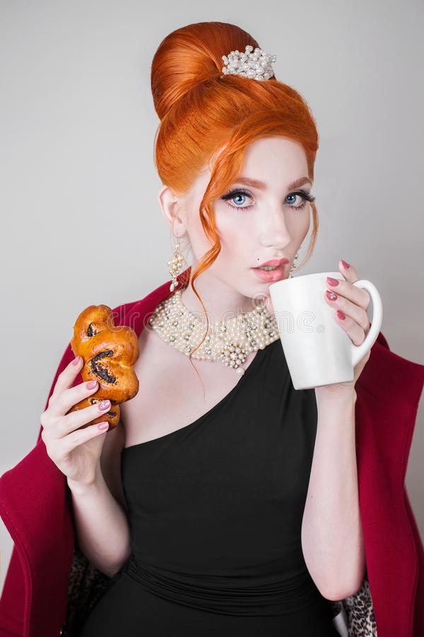 A beautiful red-haired woman with a retro-hairstyle and make-up is holding a white mug royalty free stock photos