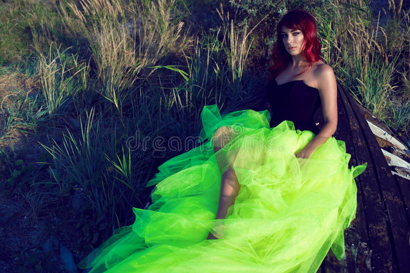 Beautiful red haired womanin black corset and long tail green veiling skirt lying on the shabby upside down wooden boat stock image