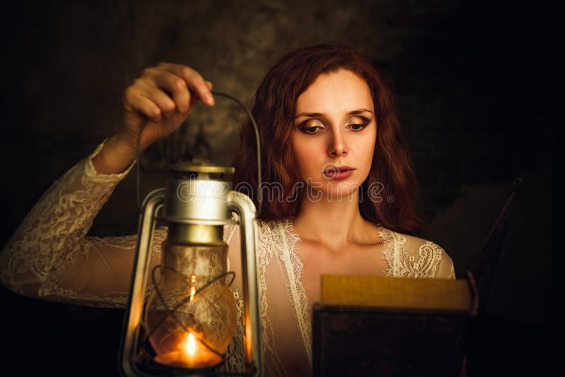 Beautiful red-haired young woman with kerosene lamp reading book stock photos