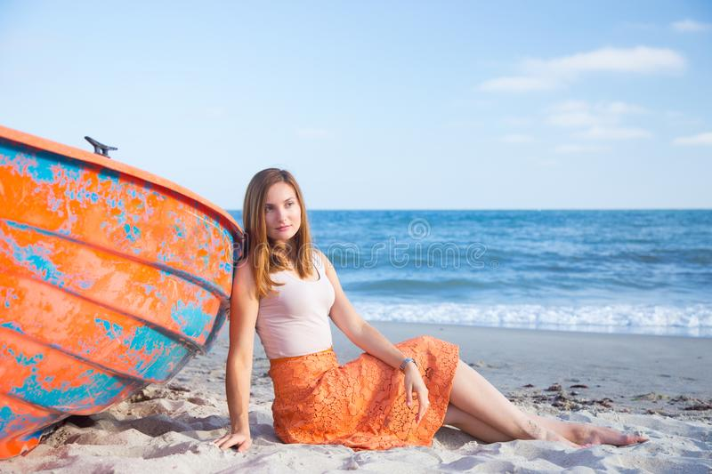 Beautiful red-haired young woman in skirt relaxing on beach near orange boat. stock photography