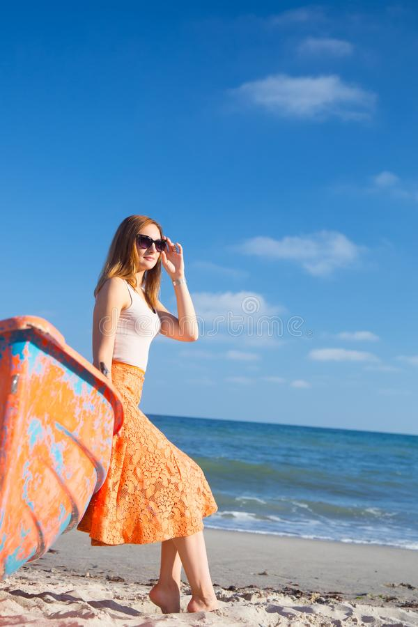 Beautiful red-haired young woman in sunglasses and skirt relaxing on beach near orange boat. stock photo