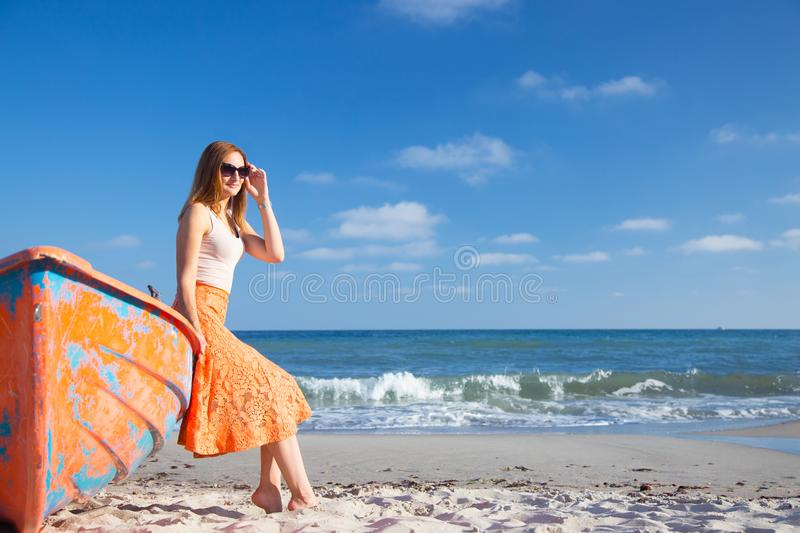 Beautiful red-haired young woman in sunglasses and skirt relaxing on beach near orange boat. royalty free stock images