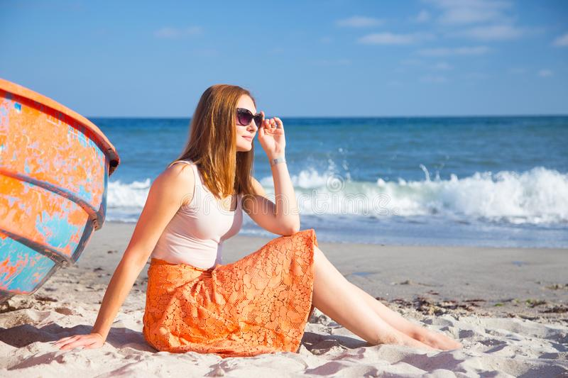 Beautiful red-haired young girl in sunglasses and skirt relaxing on beach near orange boat. royalty free stock photography