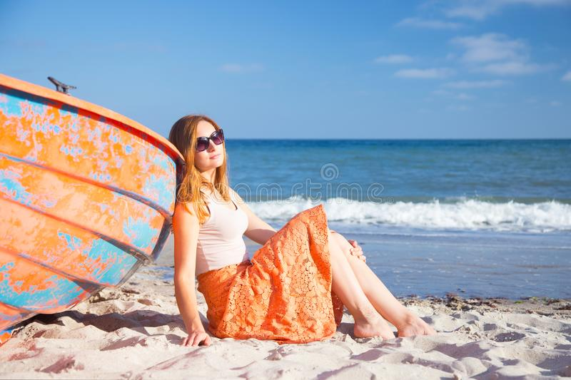 Beautiful red-haired young woman in sunglasses and skirt relaxing on beach near orange boat. royalty free stock photo