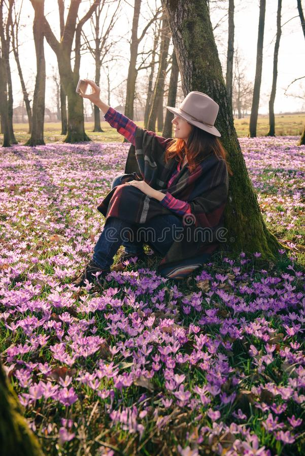 Spring crocuses in forest and a female traveler. Beautiful red head girl in a hat and colorful poncho, matching lilac crocuses around, taking selfie of Spring stock photo