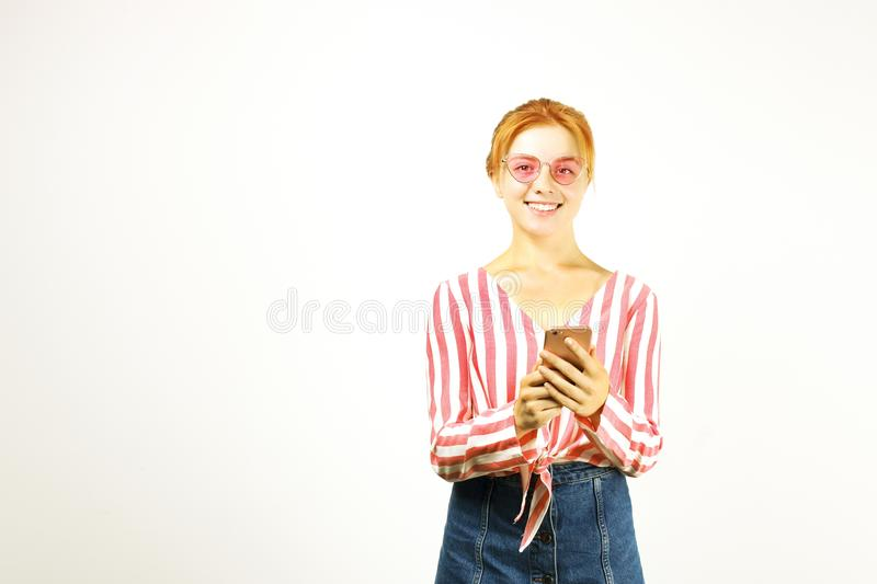 Beautiful red headed young woman posing, showing emotional facial expressions and making funny faces with mobile phone stock images