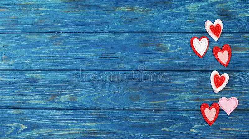 Beautiful red heart ornaments on a wooden blue background for Valentine`s Day royalty free stock images