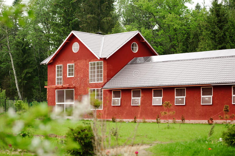 Beautiful red horse barn among the green forest royalty free stock photos