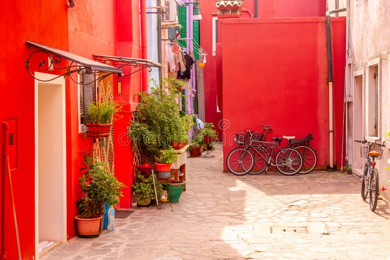 Beautiful red houses with bicycles. Colorful houses in Burano island near Venice, Italy stock images