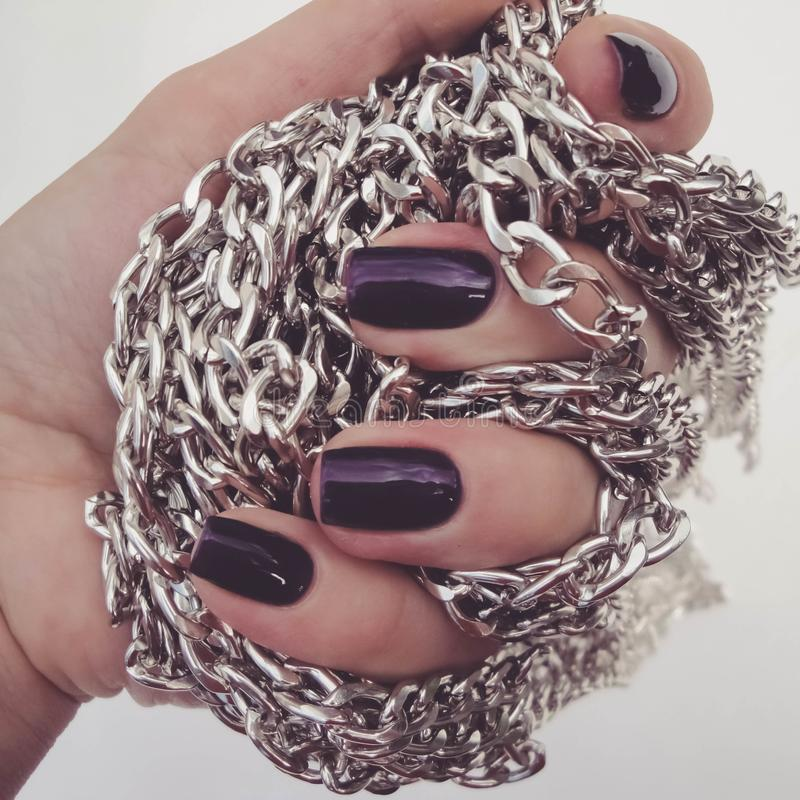 Beautiful red nails and chain close up.Beautiful, well-groomed nails with purple nail polish and chain in hand royalty free stock photo