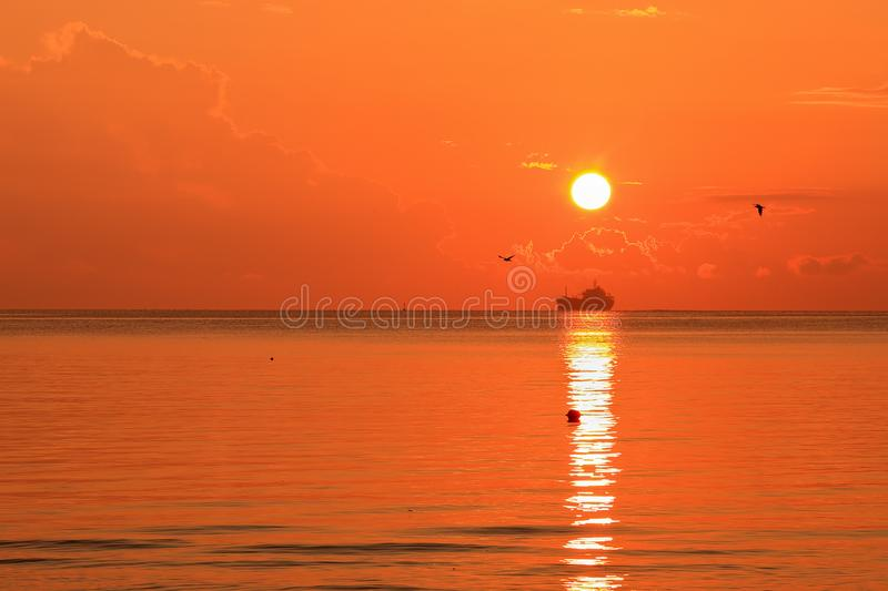 Beautiful red orange sunrise above the sea and clouds with a ship crossing the reflected in the water sun path. Asparuhovo beach, Varna, Bulgaria stock images