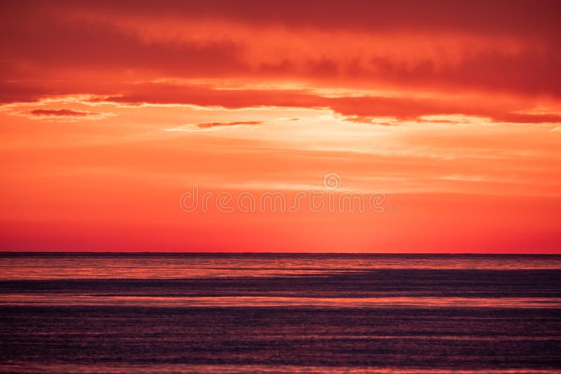 Beautiful red and orange sunset over the sea. In a cloudy sky. Dramatic Sunset Sky stock image