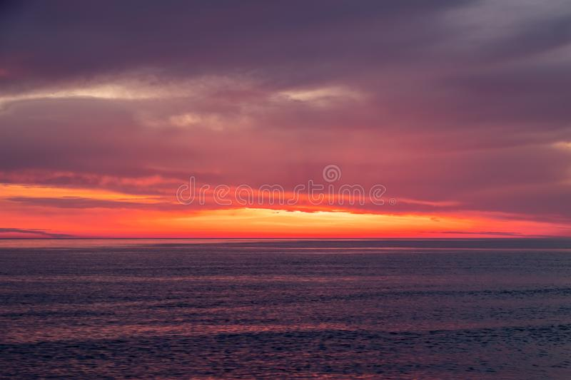 Beautiful red and orange sunset over the sea. In a cloudy sky. Dramatic Sunset Sky royalty free stock images