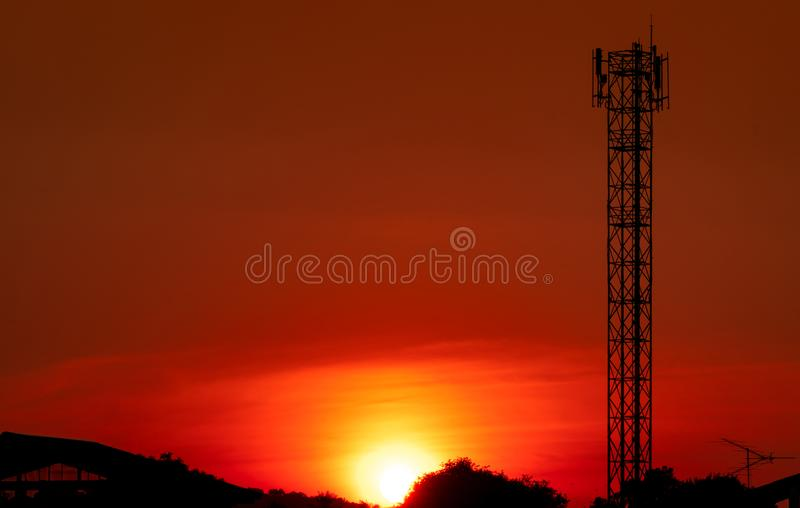 Beautiful red and orange sunset sky. Silhouette telecommunication tower and  tree in the evening with beautiful red sunset sky stock photos