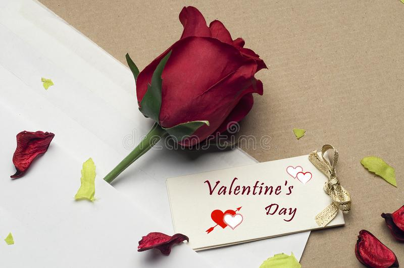 Red rose in an envelope on a light brown background stock photos