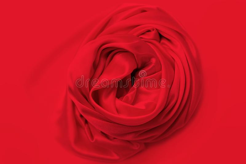 Beautiful red satin fabric draped with soft folds in a rose, silk cloth background, close-up, copy space royalty free stock images