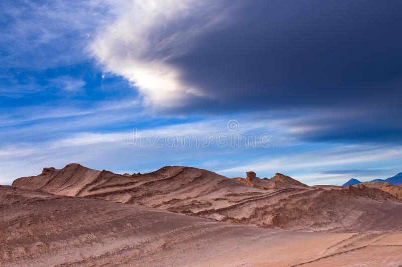 Beautiful, red stone sculptures in moon valley, atacama desert while the weather battles above it royalty free stock images