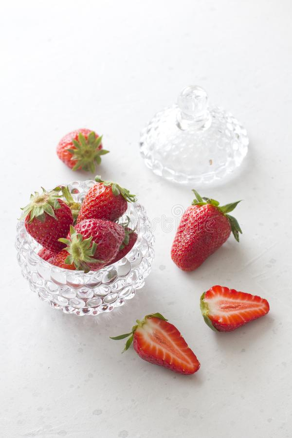 Beautiful red strawberry in glass round bowl Close up. Strawberries on a light white concrete background. Rustic style. Cut stock photos