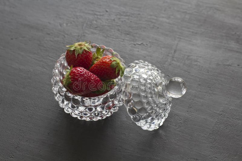 Beautiful red strawberry in glass round bowl. Strawberries on a black dark concrete background. Rustic style. Horizontal. Minimalism. Top View, Copy Space For stock photography