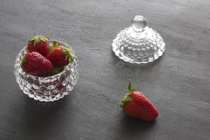 Beautiful red strawberry in glass round bowl. Strawberries on a black dark concrete background. Rustic style. Horizontal. Minimalism. Top View, Copy Space For royalty free stock photos
