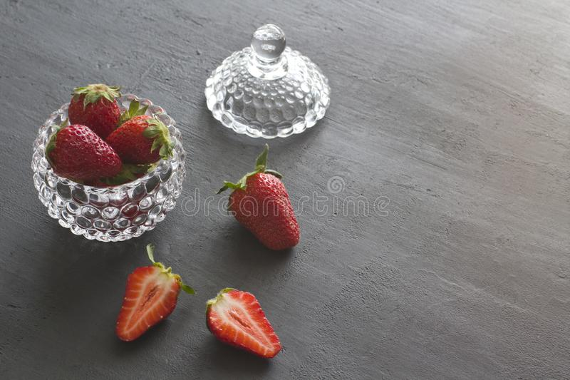 Beautiful red strawberry in glass round bowl. Strawberries on a black dark concrete background. Rustic style. Horizontal. Minimalism. Cut strawberries, half royalty free stock images