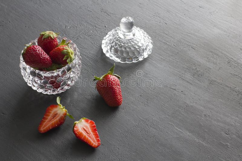 Beautiful red strawberry in glass round bowl. Strawberries on a black dark concrete background. Rustic style. Horizontal. Minimalism. Cut strawberries, half royalty free stock image