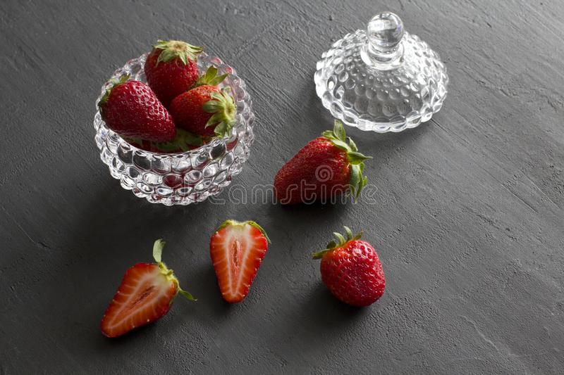 Beautiful red strawberry in glass round bowl. Strawberries on a black dark concrete background. Rustic style. Horizontal. Minimalism. Cut strawberries, half royalty free stock photography