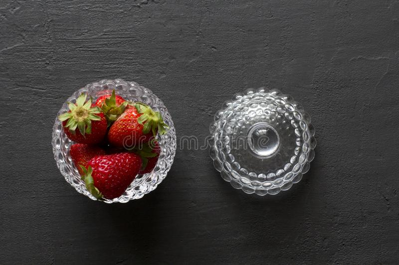 Beautiful red strawberry in glass round bowl. Strawberries on a black dark concrete background. Rustic style. Horizontal. Minimalism. Flat Lay, Top View, Copy royalty free stock image