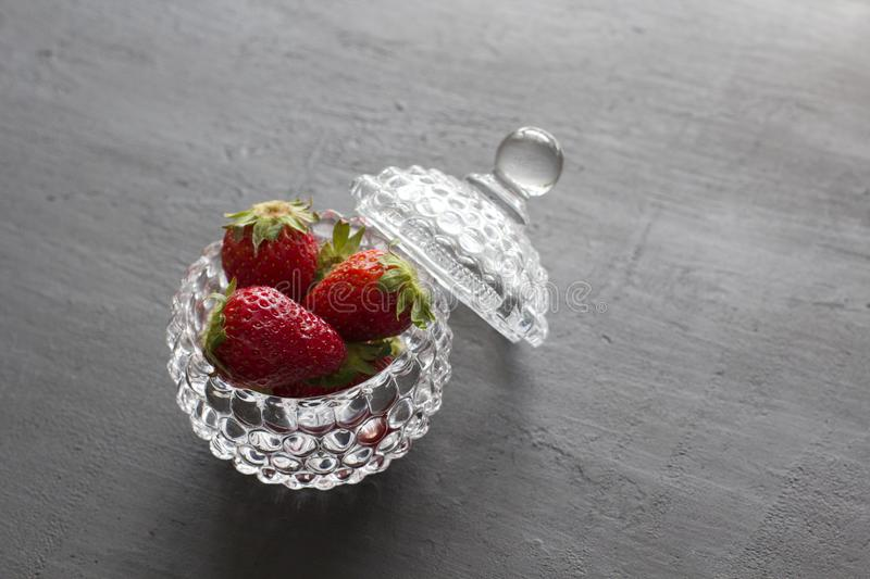 Beautiful red strawberry in glass round bowl. Strawberries on a black dark concrete background. Rustic style. Horizontal. Minimalism. Top View, Copy Space For royalty free stock images