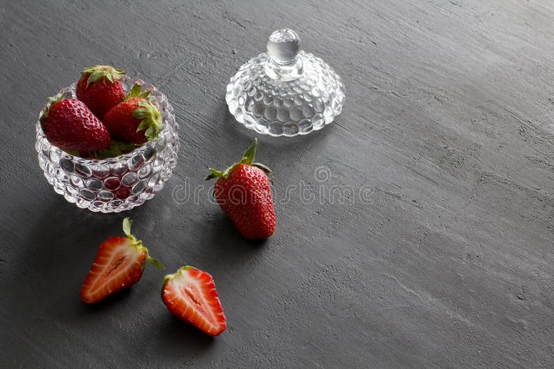 Beautiful red strawberry in glass round bowl. Strawberries on a black dark concrete background. Rustic style. Horizontal. Minimalism. Cut strawberries, half stock photos