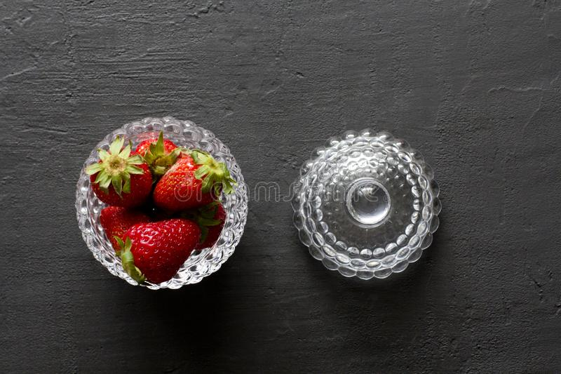 Beautiful red strawberry in glass round bowl. Strawberries on a black dark concrete background. Rustic style. Horizontal. Minimalism. Flat Lay, Top View, Copy royalty free stock images