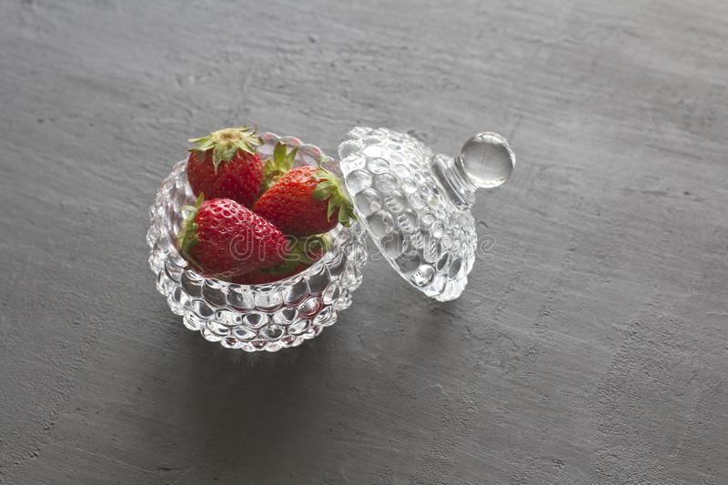 Beautiful red strawberry in glass round bowl. Strawberries on a black dark concrete background. Rustic style. Horizontal. royalty free stock photos