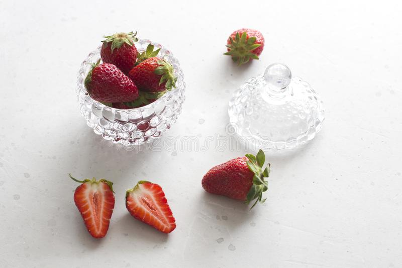 Beautiful red strawberry in glass round bowl. Strawberries on a light white concrete background. Rustic style. Cut strawberries, royalty free stock image
