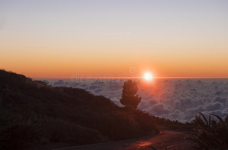 Beautiful red sunset above white clouds cover over asphhalt road over mountains at La Palma, Canary Island, Spain.  royalty free stock images