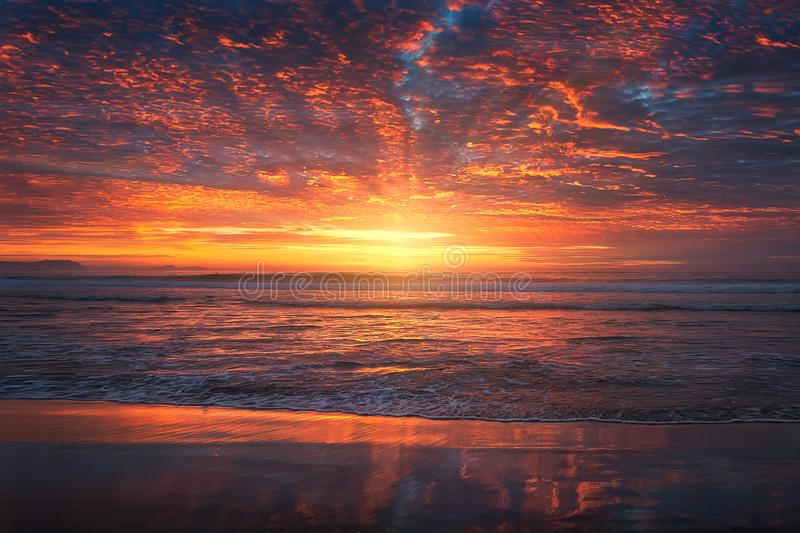 Beautiful red sunset on beach with vivid sky stock images