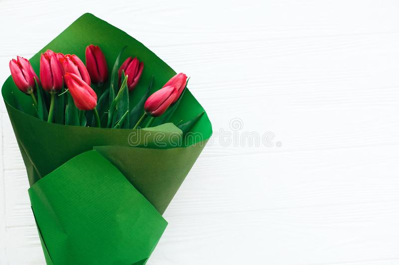 Beautiful red tulips bouquet in green paper on white wooden background flat lay. Happy mothers day. Pink tulips close up on white royalty free stock images