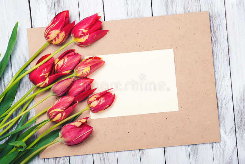 Beautiful red tulips , empty paper sheet on wooden background. Mother`s day. stock image