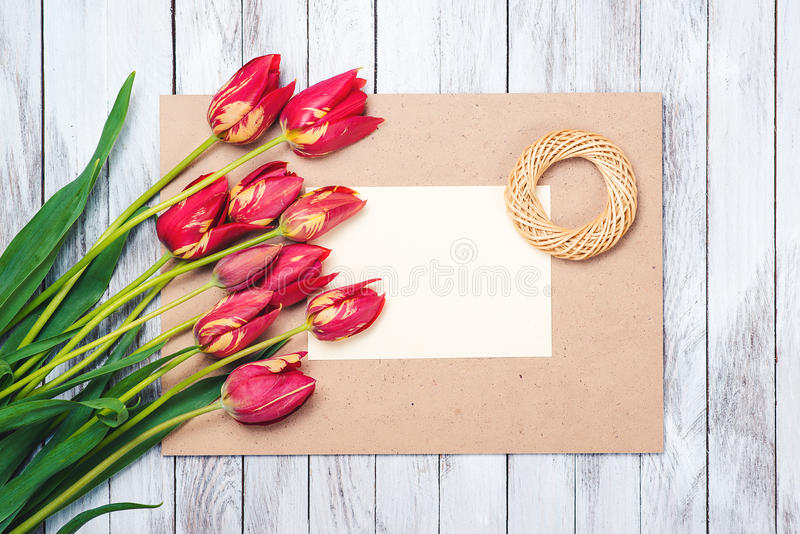 Beautiful red tulips , empty paper sheet on wooden background. Mother`s day. royalty free stock images