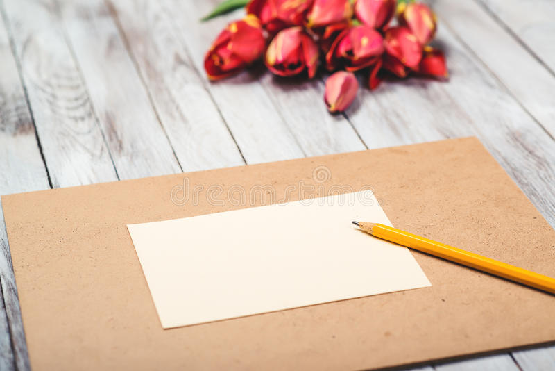 Beautiful red tulips , empty paper sheet on wooden background. Mother`s day. Selective focus. royalty free stock photography