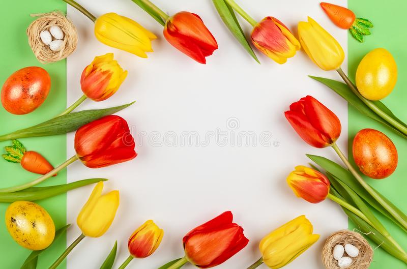 Beautiful red  tulips flowers and Easter eggs  for holiday. Beautiful red and yellow tulips flowers and Easter eggs  for holiday royalty free stock image