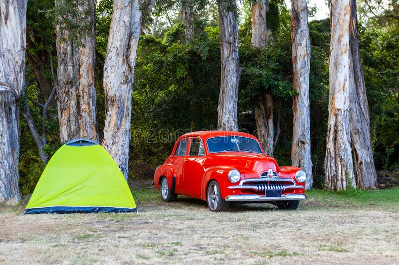 Red vintage car parked near small green tent. Beautiful red vintage car parked near small green tent royalty free stock images