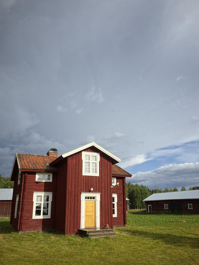 Beautiful red wood house with a cloudy sky royalty free stock photography