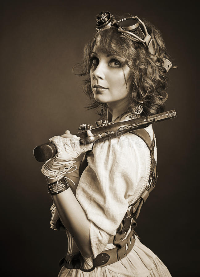 Beautiful redhair steampunk girl with gun looking at camera. Old royalty free stock photos
