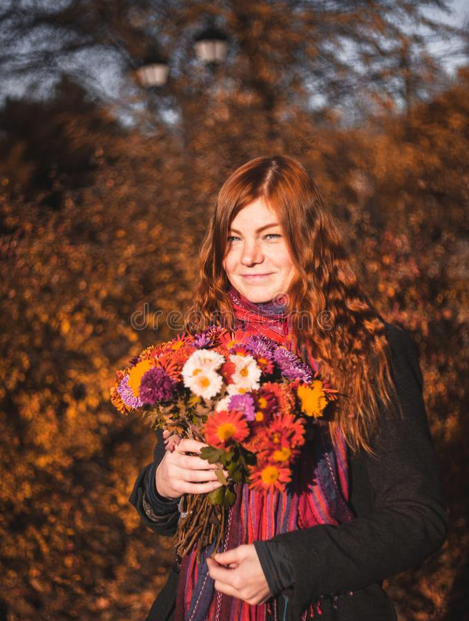 Beautiful redhaired girl with a flowers. Beautiful redhaired girl with a flowers outdoor stock photography