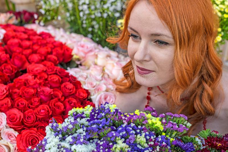 Beautiful redhead Caucasian girl smelling colorful flowers royalty free stock photography