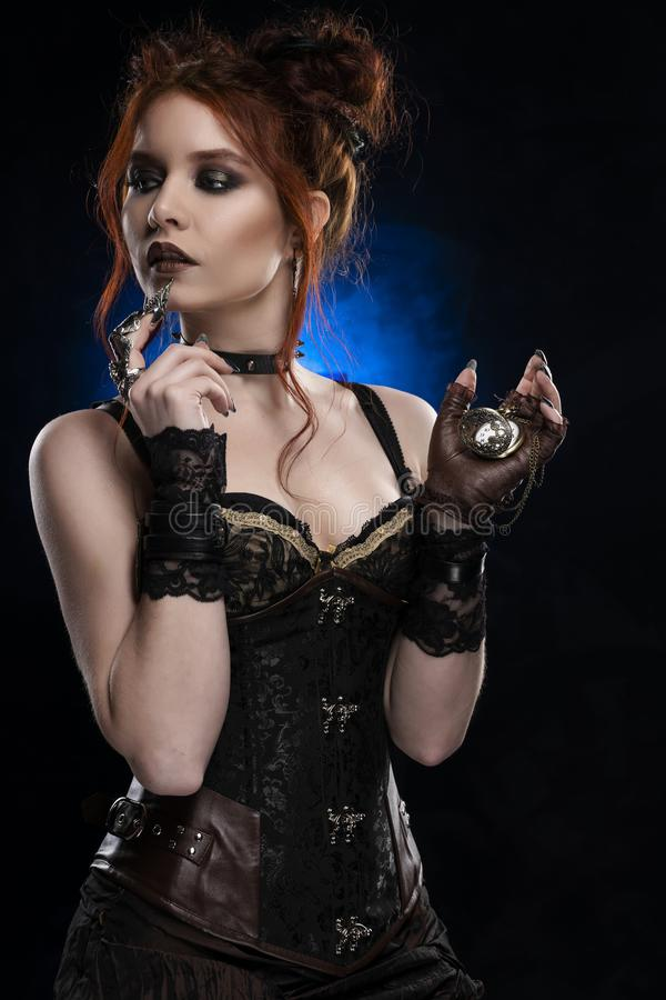 Beautiful redhead cosplayer girl wearing a Victorian-style steampunk costume with a big breast in a deep neckline holds a pocket royalty free stock images