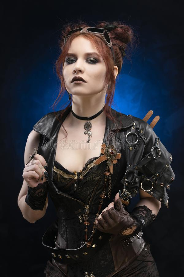 Beautiful redhead cosplayer girl wearing a Victorian-style steampunk costume with big breasts in a deep neckline boldly opens her. Vest against a black and blue royalty free stock photography