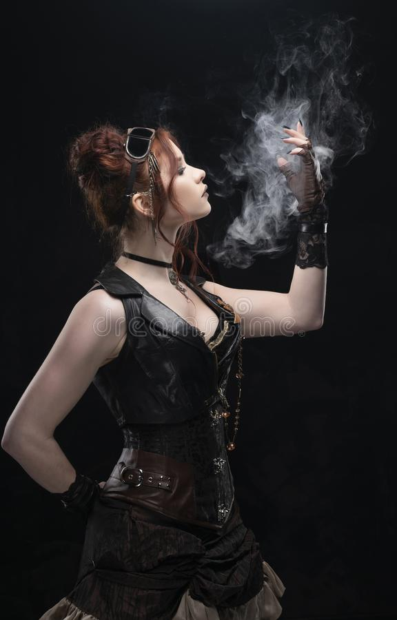 A beautiful redhead cosplayer girl wearing a Victorian-style steampunk costume with big breasts in a deep neckline holds her hand royalty free stock images