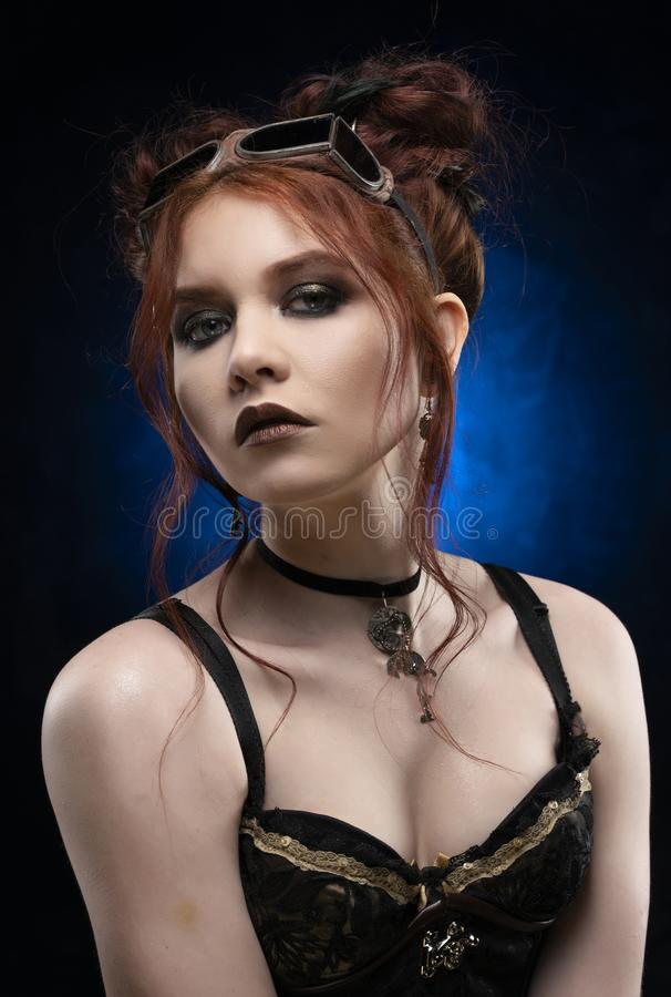 A beautiful redhead cosplayer girl wearing a Victorian-style steampunk costume with big breasts in a deep neckline. Portrait. Blue royalty free stock photography