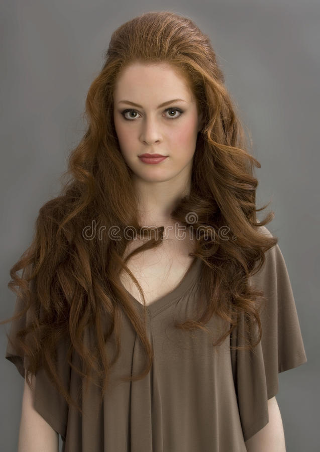 Beautiful redhead girl. In studio on a gray background stock photos